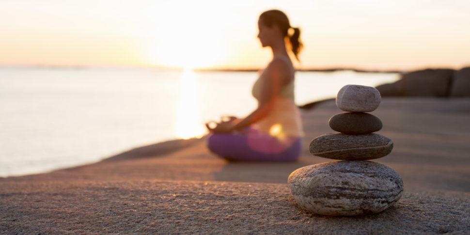 Žena sedící na pláži a meditující